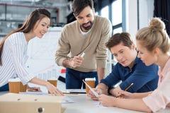 Бизнесмены обсуждая новый бизнес-план на малый officemeeting Стоковые Фото
