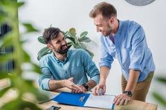 Бизнесмены обсуждая новый проект на рабочем месте в офисе Стоковые Изображения