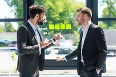 Бизнесмены обсуждая новый проект пока работающ в офисе Стоковые Фотографии RF