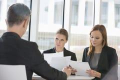 Бизнесмены обсуждая обработку документов в столовой офиса Стоковое Изображение RF