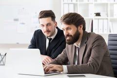 Бизнесмены обсуждая проект на компьтер-книжке Стоковые Фото