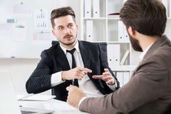 Бизнесмены обсуждая что-то в офисе Стоковые Фотографии RF
