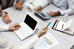Бизнесмены обсуждения на таблице используя разнообразие электронных устройств Стоковые Изображения RF