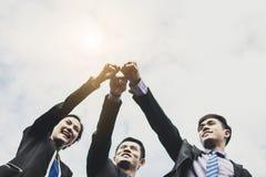Бизнесмены объединяются в команду показывающ кулак на небе, партнере и воюющ f стоковая фотография rf