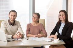 Бизнесмены объединяются в команду сидеть на столе офиса смотря камеру Стоковое фото RF
