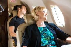 Бизнесмены ослабляя на частном самолете Стоковая Фотография
