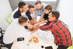 Бизнесмены показывая сыгранность в офисе Стоковое Фото