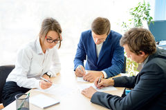 Бизнесмены подписывая контракт вокруг таблицы в современном офисе Концепция сотрудничества дела Стоковое Изображение RF