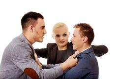 Бизнесмены получая в женщину боя пробуя отделить их Стоковое Изображение RF