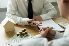 Бизнесмены представляют контракт цены на торговой операции - для того чтобы арендовать дом к клиентам Дом страхового инспектора r стоковые фото