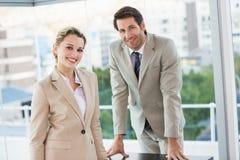 Бизнесмены представляя и усмехаясь на камере Стоковые Изображения