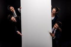 Бизнесмены представляя пустую афишу изолированную на черноте Стоковое Фото