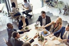 Бизнесмены приветственных восклицаний партии наслаждаясь концепцией еды Стоковое фото RF