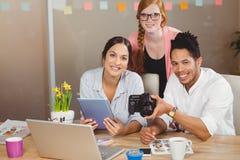 Бизнесмены при камера работая в офисе Стоковые Изображения