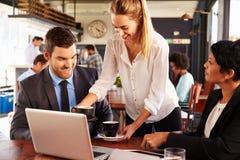 2 бизнесмены при компьтер-книжка будучи послуженным в кафе Стоковое Изображение RF