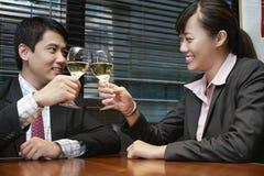Бизнесмены провозглашать рюмки на таблице кафа Стоковая Фотография