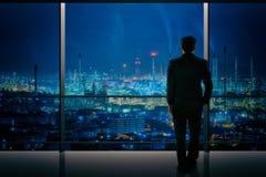 Бизнесмены проектируя стоять и смотреть нефтеперерабатывающее предприятие Стоковое Изображение RF