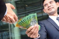 Бизнесмены проходя деньги, банкноты доллара Австралии Стоковые Изображения RF