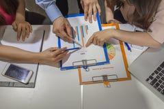 Бизнесмены пункта на диаграмме в то же время стоковые изображения rf