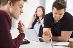 Бизнесмены планируя пока коллега используя умный телефон Стоковые Изображения