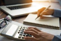Бизнесмены работают на калькуляторе и компьтер-книжке в деле Стоковые Изображения