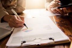 Бизнесмены работают на учете в анализе возможностей производства и сбыта с диаграммами и документацией Стоковые Изображения RF