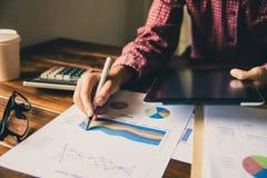 Бизнесмены работают на учете в острословии анализа возможностей производства и сбыта Стоковое Изображение RF