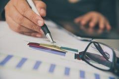 Бизнесмены работают на учете в острословии анализа возможностей производства и сбыта Стоковое Изображение