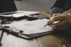 Бизнесмены работают на учете в острословии анализа возможностей производства и сбыта Стоковое Фото