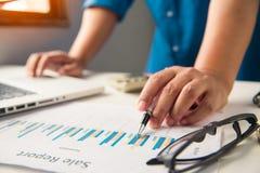 Бизнесмены работают на учете в острословии анализа возможностей производства и сбыта Стоковые Изображения RF