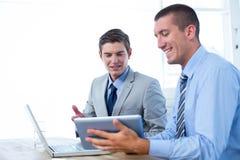 Бизнесмены работая вместе с компьтер-книжкой и таблеткой Стоковое фото RF