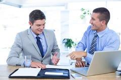 Бизнесмены работая вместе с компьтер-книжкой Стоковое Фото