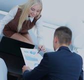 Бизнесмены работая вокруг таблицы в современном офисе Стоковое Изображение