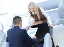 Бизнесмены работая вокруг таблицы в современном офисе Стоковое Фото