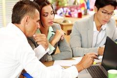 Бизнесмены работая вокруг таблицы Стоковая Фотография RF