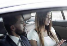 2 бизнесмены работая в задней части автомобиля Стоковые Изображения RF