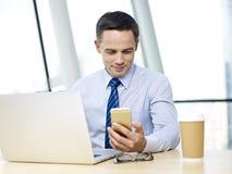 Бизнесмены работая в офисе с мобильным телефоном и компьтер-книжкой Стоковые Фото