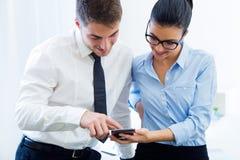 Бизнесмены работая в офисе с мобильным телефоном Стоковое Изображение