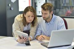 Бизнесмены работая используя таблетку и компьтер-книжку Стоковые Изображения RF