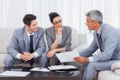 Бизнесмены работая и говоря совместно на софе Стоковое Изображение