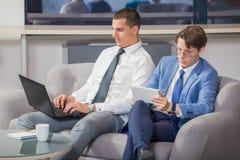 Бизнесмены работая и сидя на софе Стоковая Фотография