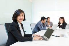 Бизнесмены работая на компьтер-книжке в конференц-зале Стоковое Изображение