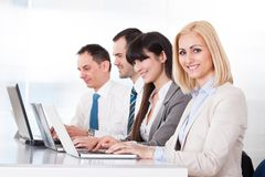 Бизнесмены работая на компьтер-книжке в офисе Стоковое Изображение