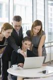 Бизнесмены работая на компьтер-книжке в столовой офиса Стоковая Фотография