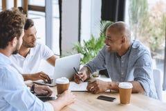 Бизнесмены работая на компьтер-книжке и обсуждая стратегию бизнеса в офисе Стоковое фото RF