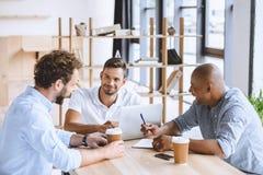 Бизнесмены работая на компьтер-книжке на встрече в офисе Стоковые Изображения RF
