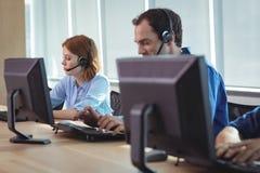 Бизнесмены работая на компьютере в центре телефонного обслуживания Стоковые Изображения RF