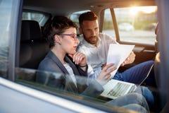 Бизнесмены работая на обработке документов в заднем сиденье автомобиля Стоковые Изображения