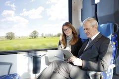 Бизнесмены работая на поезде Стоковые Фото
