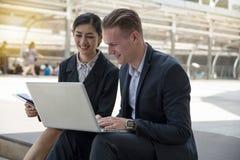 Бизнесмены работая на тетради и обсуждая на бизнес-плане Стоковые Изображения RF